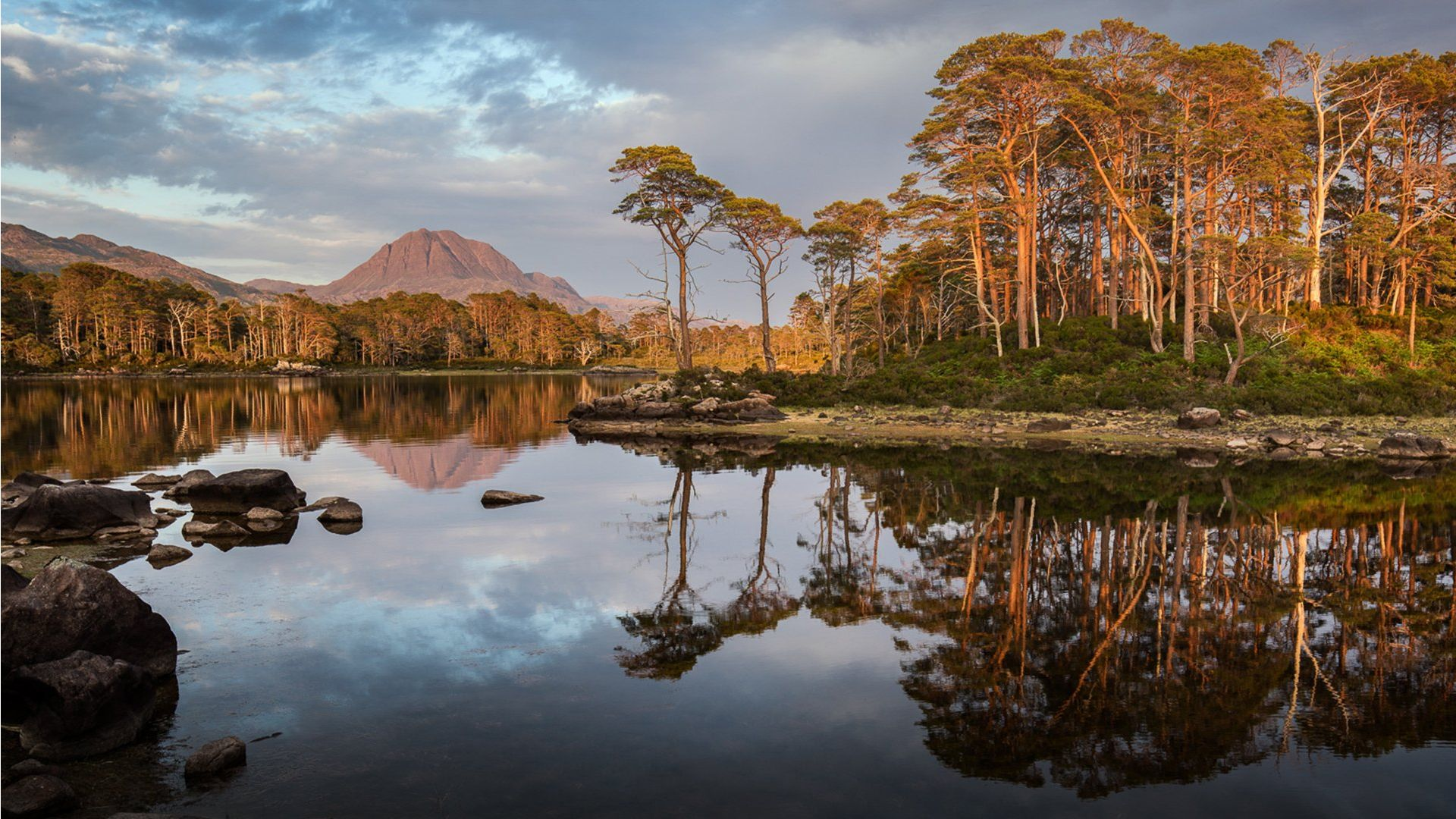Trees reflect in a lake in Scotland with a mountain in the background